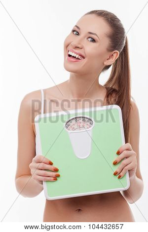 Cheerful young woman is carrying weighing machine
