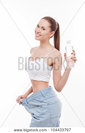 Attractive young woman with big jeans and drink