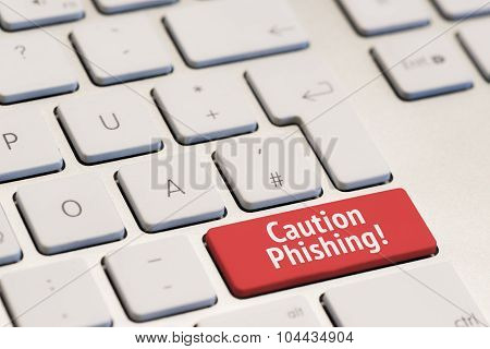 computer keyboard with the words caution phishing on red key
