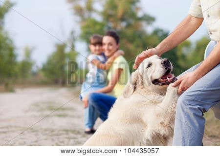 Cheerful friendly family and puppy are resting in park