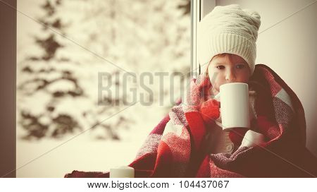 Child Little Girl With  Cup Of Hot Tea At Window And Looking At The Winter Forest