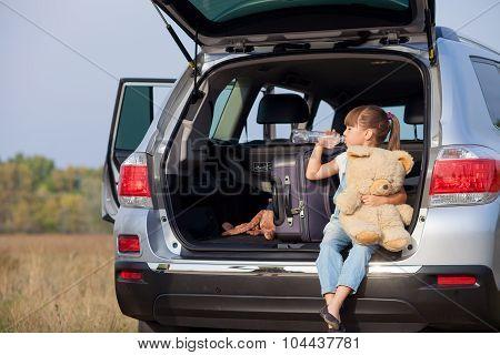 Cute small female child near transport in meadow