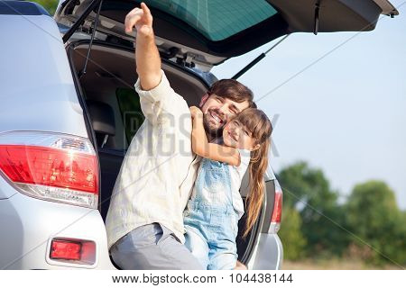 Cheerful father with child in forest near vehicle