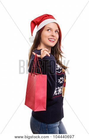 Girl In Winter Clothes Wearing Santa's Hat And Holding A Shopping Bag