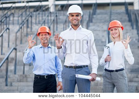 Skillful construction team is gesturing with positive emotions