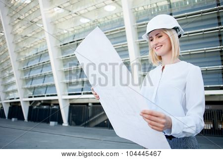 Attractive young female engineer is watching sketch of building