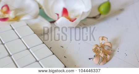 Closeup Of Earrings Next To White Keyboard And Flower