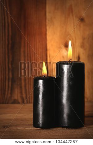 Black burning candles on wooden background. Symbols of witchcraft. Halloween