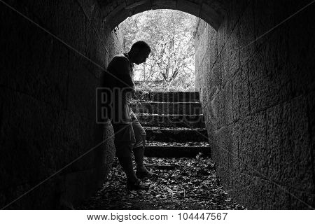Young Sad Man Stands In Dark Stone Tunnel