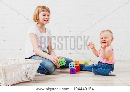Litle girl clap her hands nearby cubes with dots