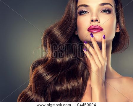 Beautiful model brunette with long curled hair. Violet manicured nails  and fashion makeup