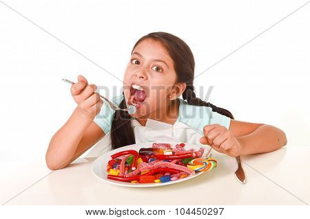 Happy Latin Female Child Eating Dish Full Of Candy And Gummies With Fork And Knife And Big Cola Bott
