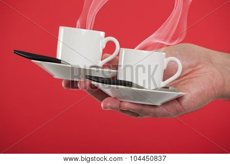 Hand holding espresso cups
