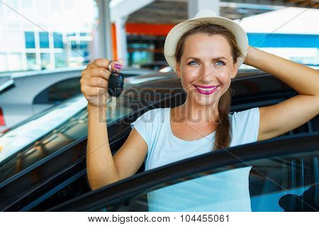 Happy Woman Standing Near A Car With Keys In Hand - Concept Of Buying A Used Car