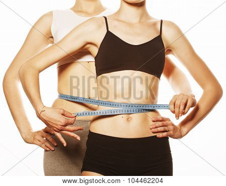 two sport girls measuring themselves isolated on white