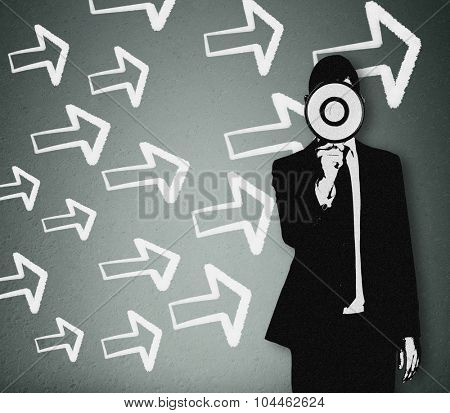 Young business man with loudspeaker and arrows pointing right