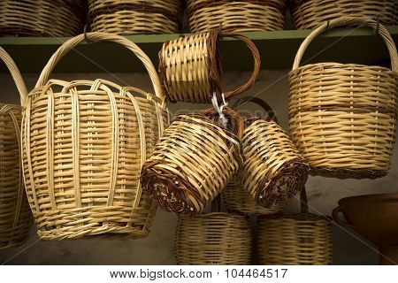 Straw baskets on sale hang on a wall in a market