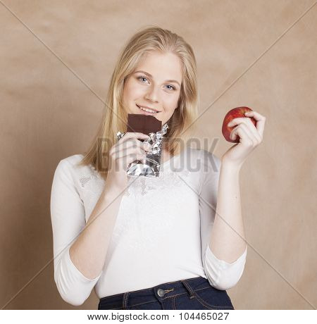 young beauty blond teenage girl eating chocolate smiling, choice between sweet and apple
