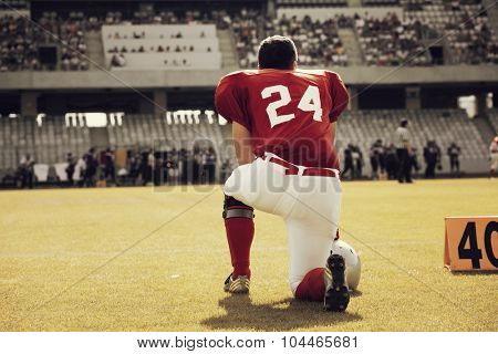 American football player on its knee - retro styled photo
