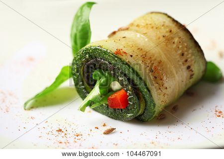 Zucchini roll with cheese, bell peppers and arugula on plate, close-up