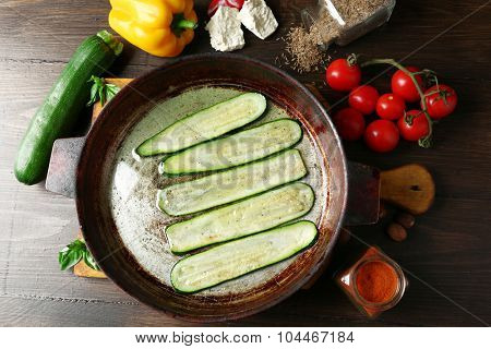 Fresh ingredients and fried zucchini slices for preparing zucchini rolls on wooden background