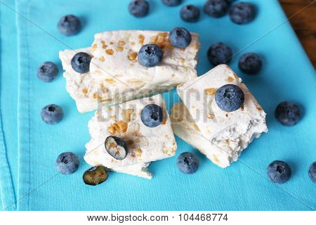 Sweet nougat with nuts and blueberries on napkin close up