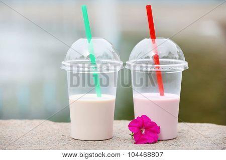 Plastic cups of milkshake on light background, outdoors