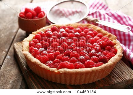 Tart with fresh raspberries, on wooden background