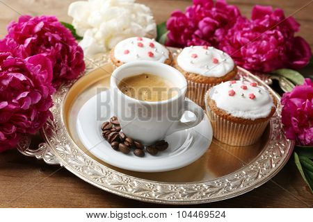 Composition with cup of coffee, muffins and peony flowers on tray, on wooden background
