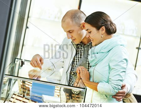 Young happy couple together selecting gold gift at jewelry boutique shop