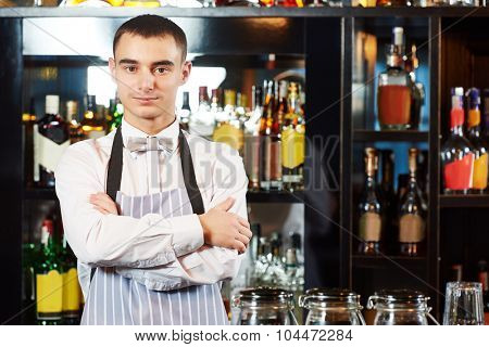 Portrait of young barman worker at bartender desk in restaurant bar