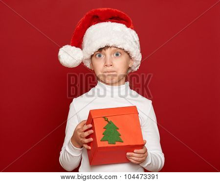 winter, child,  christmas concept - surprised girl in santa helper hat with box gift on red background