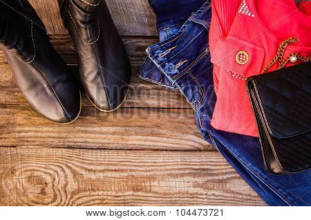 Women's clothing and accessories: sweater, jeans, handbag, shoes, beads on wooden background.