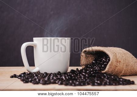 Cup Of Coffee With Roasted Coffee On A Dark Wooden And Smoke