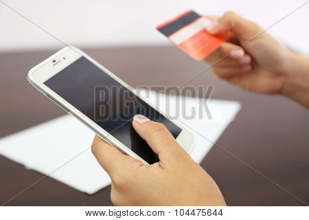 Woman verifies account balance on smartphone with mobile banking application on wooden table background
