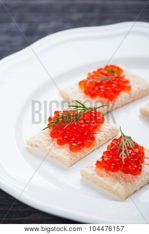Toasts with red caviar on wooden background