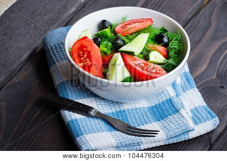 Salad with fresh vegetables on wooden rustic background. Salad with tomato, cucumbers, olives and herbs