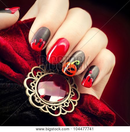Halloween Nail art design. Nail Polish. Beauty hands. Trendy Stylish Colorful Nails and Nailpolish. Black matte nailpolish with blood drips and pumpkin