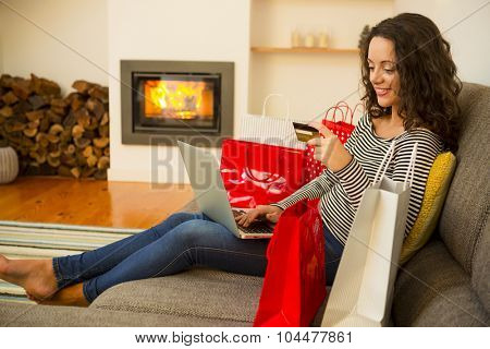 Beautiful woman at home at the warmth of the fireplace, shopping online