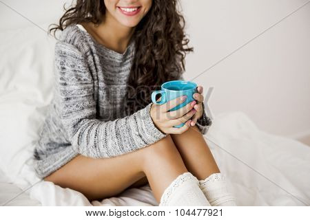 Beautiful woman on bed drinking a coffee