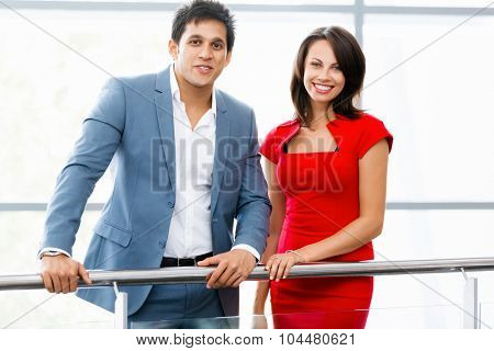 Two young business collegue standing in office