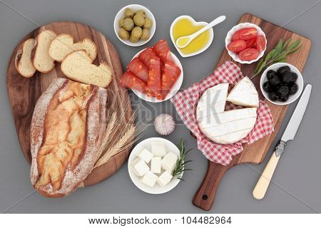 Fresh food selection with chorizio, camembert and feta cheese, olives, tomatoes, oil, herbs and rustic bread on maple boards.