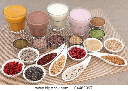 Health and body building high protein super food with supplement powders with orange, chocolate whey, red maca and acai berry smoothies, fruit, grains, seeds, pulses and nuts over white background.