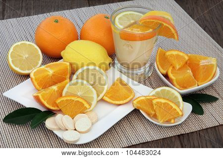 Cold and flu health remedy drink with orange and lemon fruit and vitamin c tablets on bamboo over oak background.