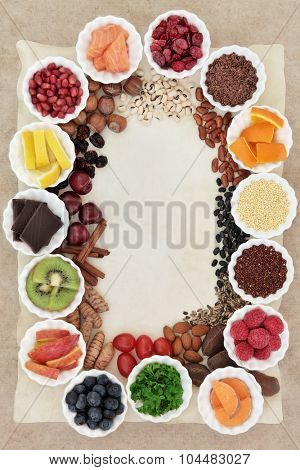 Superfood collection background border in porcelain bowls and loose over parchment and hemp paper. High in vitamins and antioxidants.
