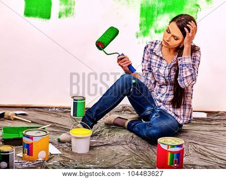 Unhappy sad tired woman paint wall at home.