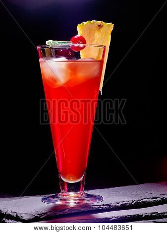 Red  drink  with cherry and pineapple in highball glass . Black Cocktail card 84.