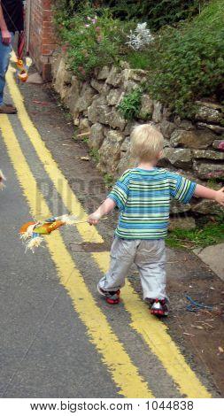Boy Walking Carrying Scarecrow
