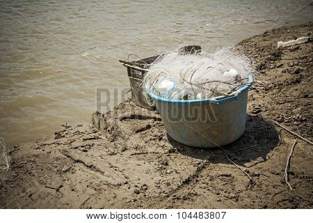 Blue Plastic Bucket Is Full Of Fishing Net.
