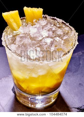 Yellow cube ice of cold drink  with  pineapple on dark background. Cocktail card 85.